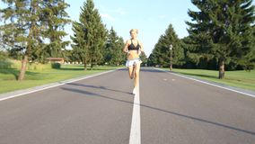 A beautiful fit and healthy blond woman road running down a suburban street in summer sunshine. 4k stock video footage