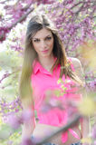 Beautiful fit lady between blossom tree in purple color Royalty Free Stock Image