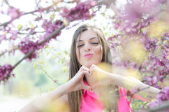 Beautiful fit lady between blossom tree in purple color Stock Photos