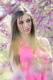 Beautiful fit lady between blossom tree in purple color Royalty Free Stock Photography