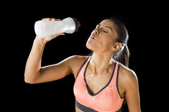 Beautiful and fit latin sport woman drinking water tired during training workout Royalty Free Stock Photography
