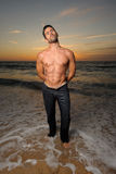Beautiful fit man at the beach stock images