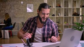 Beautiful fit man, caucasian appearence with black beard is sitting at workplace and typing on computer with small stock video footage