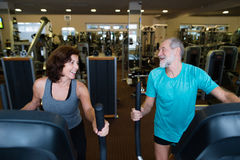 Beautiful fit senior couple in gym doing cardio work out. Royalty Free Stock Photos