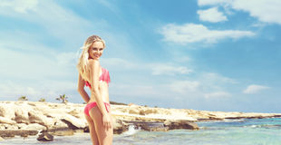Beautiful, fit and girl in pink swimsuit posing on a beach Stock Photography