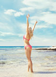 Beautiful, fit and girl in pink swimsuit posing on a beach Stock Images