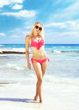 Beautiful, fit and girl in pink swimsuit posing on a beach Stock Photo