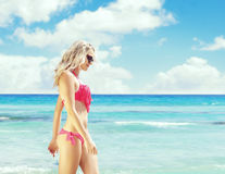 Beautiful, fit and sexy girl in pink swimsuit posing on a beach Royalty Free Stock Photography