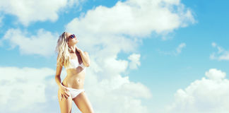 Beautiful, fit and girl in white bikini posing on a beach a Stock Photography