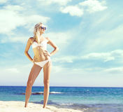 Beautiful, fit and girl in white bikini posing on a beach a Stock Photos