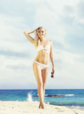 Beautiful, fit and girl in white bikini posing on a beach a Royalty Free Stock Image
