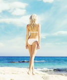 Beautiful, fit and girl in white bikini posing on a beach a Royalty Free Stock Photography