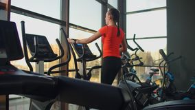 Beautiful fit sportive positive young woman in gym doing exercises on elliptical trainer working out. Slow motion, the