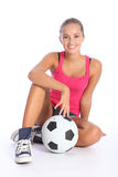 Beautiful fit teenage soccer player girl and ball. Fit young teenage athlete sitting on floor with soccer ball with beautiful smile wearing pink vest and denim Stock Photography