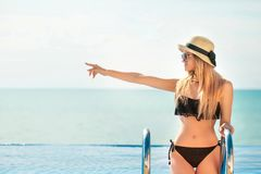 Beautiful fit woman in black swim suit and hat posing on the beach. Summer vacation. Model pointing on copy space. royalty free stock image