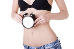 Beautiful fit woman with clock on belly Royalty Free Stock Image