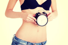 Beautiful fit woman with clock on belly Royalty Free Stock Photography