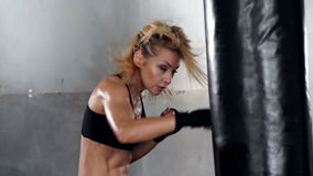 A beautiful and fit woman has a kickboxing training.
