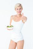 Beautiful fit woman holding a bowl of salad with thumbs up. On white background Royalty Free Stock Image