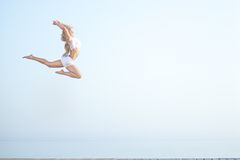 Beautiful fit woman  jumping at the beach near. Sport woman jumping against beautiful sea. Freedom, enjoyment concept Stock Images