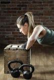 Beautiful fit woman pushing up on brick background Stock Photography