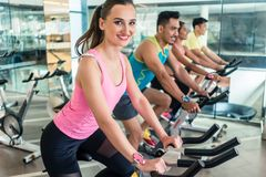 Beautiful fit woman smiling during cardio workout at indoor cycl. Side view of a beautiful fit young women smiling while pedaling during cardio workout at indoor Royalty Free Stock Images