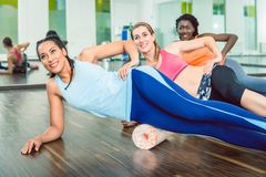 Beautiful fit woman smiling during group workout class of foam r. Beautiful fit women smiling while wearing blue fitness sleeveless top and leggings during group royalty free stock image