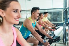 Beautiful fit woman smiling during workout at indoor cycling group class Royalty Free Stock Images