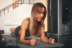Slim fitness young woman Athlete girl doing plank exercise at gym royalty free stock images