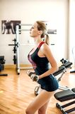 Beautiful fit girl in sportswear is engaged with dumbbells in gy Stock Photos