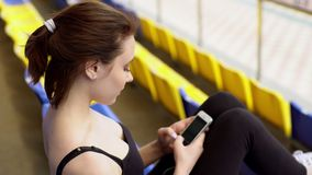 Beautiful fit woman surfing the Internet on smartphone on tribune. Young woman is using smartphone for surfing the Internet while sitting on a stadium tribune stock footage