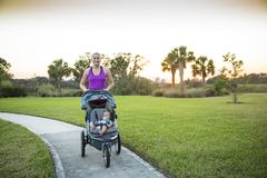 Woman jogging and exercising outdoors while pushing her baby in a stroller. Beautiful, fit women walking and jogging outdoors along a paved sidewalk in a park royalty free stock images
