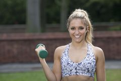 Stunning young blonde woman works out in yard. Beautiful and fit young Caucasian woman works out in front yard of home - fitness model Royalty Free Stock Photography