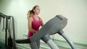 Attractive caucasian girl running on the treadmill in the sport gym. Beautiful fit young woman in a gym doing exercises on a running track stock footage