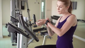 Beautiful fit young woman in gym doing exercises on a velosimulator. Using her smartwatch, browsing stock video