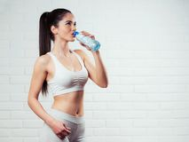 Beautiful, fit, young woman holding a bottle of water. Over a brick wall background Stock Image