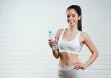 Beautiful, fit, young woman holding a bottle of water. Over a brick wall background Stock Photo