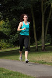 Beautiful fit young woman running in the park Royalty Free Stock Image