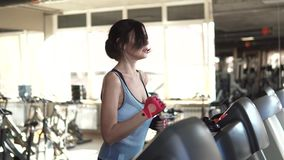 Beautiful fit young woman in sports in the gym. the girl on the treadmill. Girl running on the treadmill in the fitness room. young woman doing aerobic exercises stock video