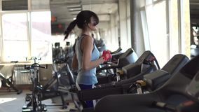 Beautiful fit young woman in sports in the gym. the girl on the treadmill. Girl running on the treadmill in the fitness room. young woman doing aerobic exercises stock footage