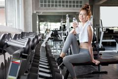 Beautiful fit young woman with white towel over his shoulder sit. Ting on a bench drinking water after exercise in fitness gym .  sport girl resting after Royalty Free Stock Photography