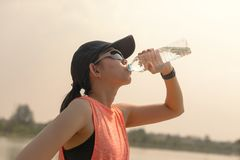 Beautiful fitness athlete woman drinking water after work out exercising on. evening summer stock photo
