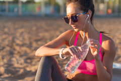 Beautiful fitness athlete woman drinking water after work out exercising on sunset evening summer in beach outdoor Stock Image