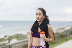 Beautiful fitness athlete woman resting drinking water after workout Stock Photography