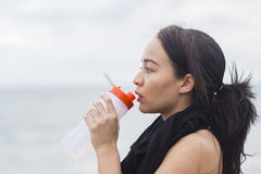 Beautiful fitness athlete woman resting drinking water after workout Stock Photos