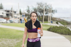 Beautiful fitness athlete woman resting drinking water after workout Royalty Free Stock Photo