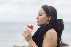 Beautiful fitness athlete woman resting drinking water after workout Royalty Free Stock Photography