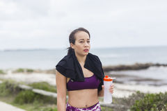 Beautiful fitness athlete woman resting drinking water after workout Royalty Free Stock Photos
