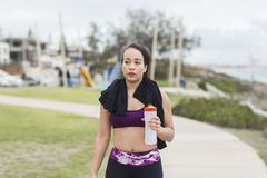 Beautiful fitness athlete woman resting drinking water after workout Royalty Free Stock Image