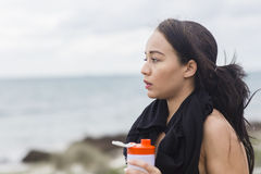 Beautiful fitness athlete woman resting drinking water after workout Royalty Free Stock Images